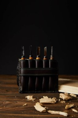 closeup shot of chisels in leather case and wooden pieces on table