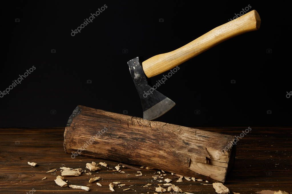 log with sticking axe and wooden pieces at table on black background