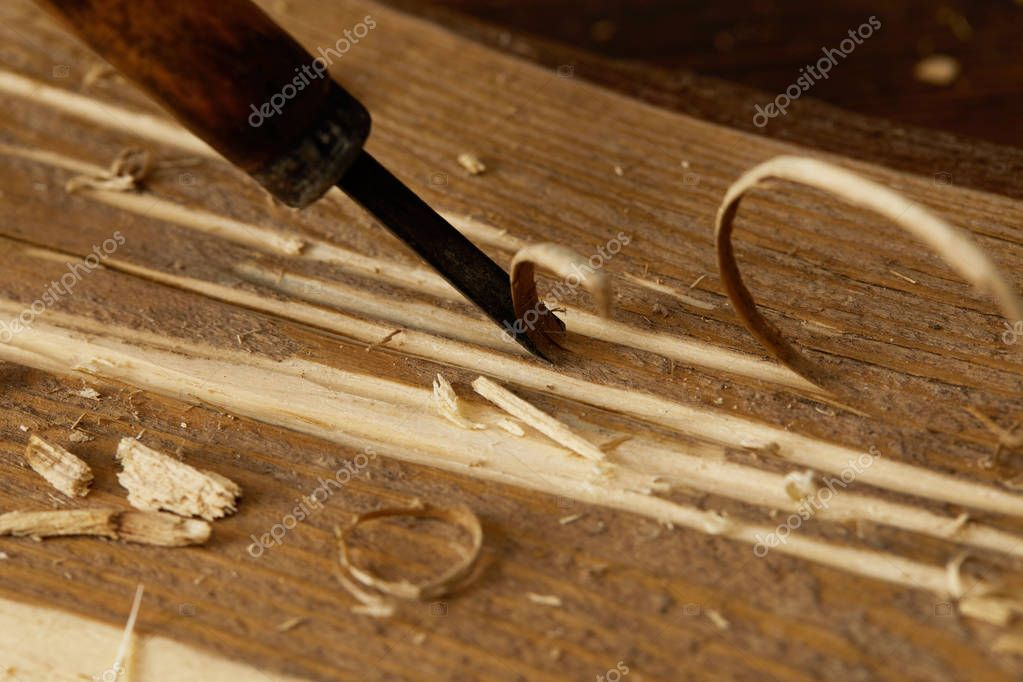 partial view of chisel sticking in wooden plank with scobs
