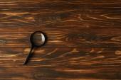 Fotografie pohled shora jediné černé lupy s rukojetí na dřevěný stůl