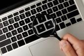 Fotografie oříznutý snímek držitele lupy nad klávesnici notebooku