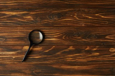 top view of single black magnifying glass with handle on wooden table