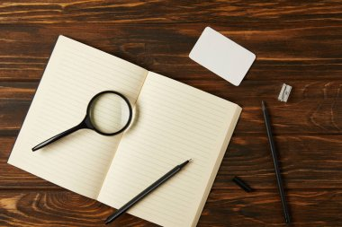 top view of magnifying glass, blank notebook and office supplies on wooden table