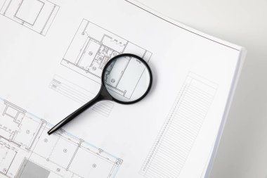 top view of magnifying glass and blueprint on grey, architecture concept
