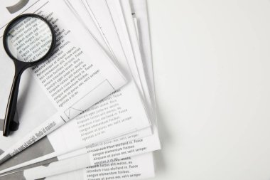 top view of magnifying glass and newspapers on grey, information concept