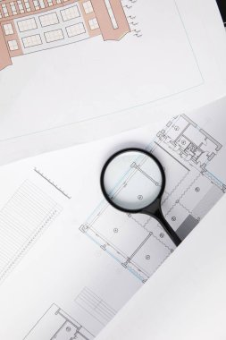 top view of magnifying glass and blueprints, architecture concept