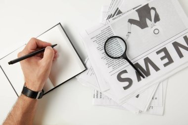 partial top view of person writing in blank notebook and magnifying glass on newspapers on grey