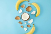 Fotografie top view of arranged coconut pieces and bananas isolated on blue