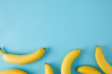 top view of arranged fresh bananas isolated on blue