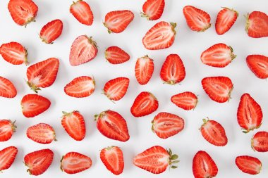 top view of arranged fresh strawberries pieces isolated on white