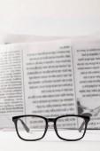 Selektivní fokus černé brýle a noviny na pozadí, černé a bílé