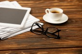 cup of coffee eyewear, digital tablet and pile of newspapers on wooden background