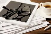 brýle, šálek kávy, digitální tabletu a noviny na dřevěný stůl