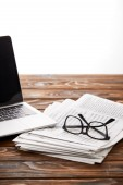 eyewear on pile of newspapers and laptop on wooden table, on white