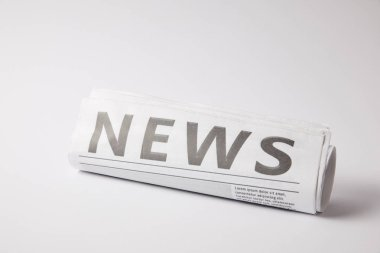 rolled newspaper lying on white background
