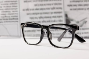 selective focus of eyeglasses and newspaper on background