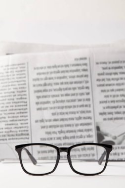 Selective focus of black eyewear and newspaper on background, black and white stock vector