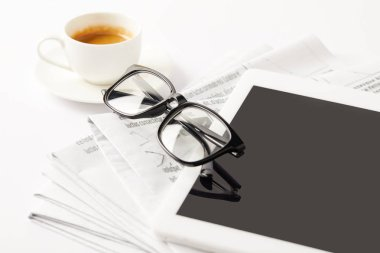 eyeglasses, coffee cup, digital tablet and pile of newspapers, on white
