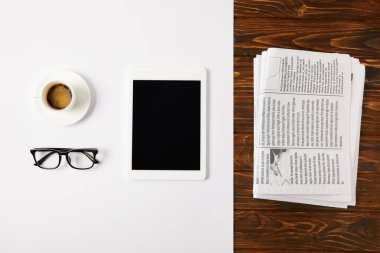 top view of eyeglasses, coffee cup, and digital tablet with blank screen on white and pile of newspapers on wooden background