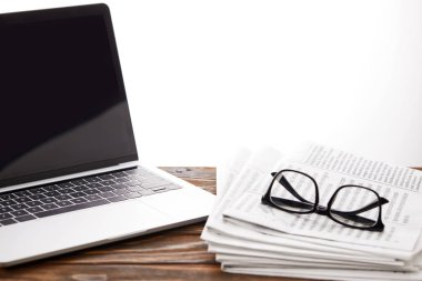 eyeglasses on newspapers and laptop with blank screen on wooden surface, on white