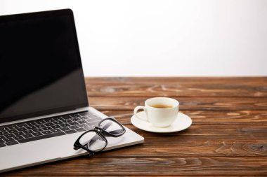 laptop with blank screen, eyeglasses and cup of coffee on wooden surface