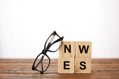 eyeglasses and alphabet cubes making word news on wooden surface, on white background