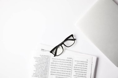 top view of eyeglasses, laptop and newspapers on white table