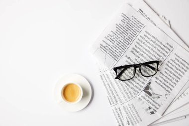 top view of cup of coffee and eyeglasses on newspapers, on white table