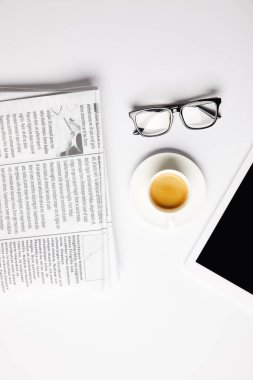 flat lay with eyeglasses, coffee, digital tablet and newspapers, on white