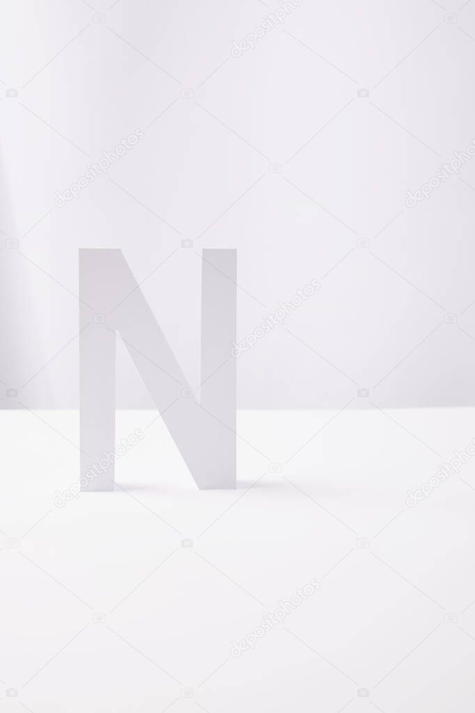 letter N made of paper, on white background with copy space