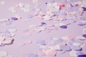 Selektivní fokus konfety kusů na fialovou povrchu