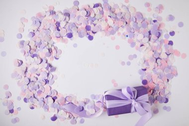 top view of gift box and violet confetti pieces on white surface