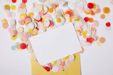 top view of confetti pieces, white paper and yellow envelope on white surface