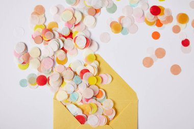top view of colored confetti pieces and yellow envelope on white surface