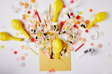 top view of confetti pieces, balloons and yellow envelope on white surface