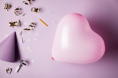 top view of heart shaped balloon, party hat and confetti pieces on surface
