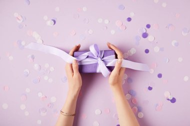 cropped image of woman holding present box at table with confetti pieces