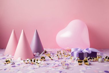heart shaped balloon, party hats and present on violet tabletop