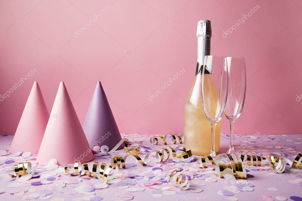 bottle of champagne, party hats and confetti pieces on violet table at party