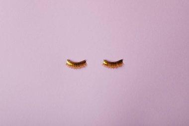 top view of stylish golden false eyelashes isolated on purple