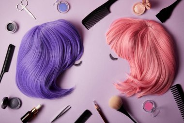 top view of pink and violet wigs, false eyelashes, makeup tools and cosmetics on purple