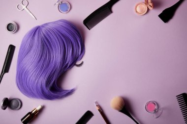 top view of violet wig, makeup tools and cosmetics on purple