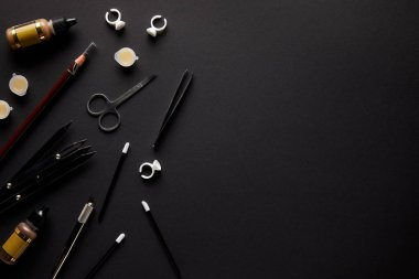 elevated view of scissors, pencil and brushes for permanent makeup isolated on black