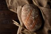 Fotografia vista superiore del pane, grano e tela su tavola di legno rustica