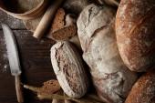 Fotografia vista elevata di vari tipi di pane, grano, mattarello, il setaccio e cilicio sulla tavola di legno