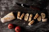 pohled shora plátky bagety, rajčat a nůž na dřevěný stůl podkladě mouky