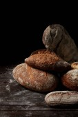 closeup view of various types of bread on wooden table covering by flour