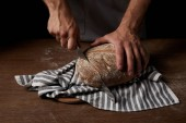 Fotografie partial view of male baker cutting bread by knife on sackcloth on wooden table