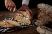 Oříznout záběr mužské baker řezání chleba nožem v žíně na dřevěný stůl