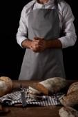 Fényképek vágott lövés a férfi baker kötény állandó tábla közelében, kést, ezerkétszázhatvan és kenyér